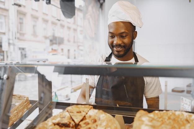Piekarz urządza gablotę w piekarni. sprzedaż produktu klientowi.