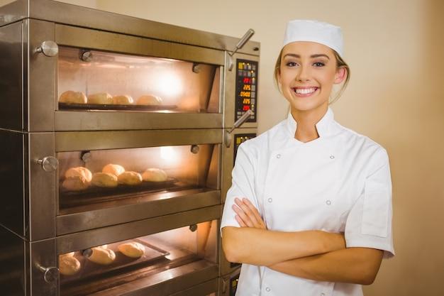 Piekarz uśmiecha się do kamery obok pieca