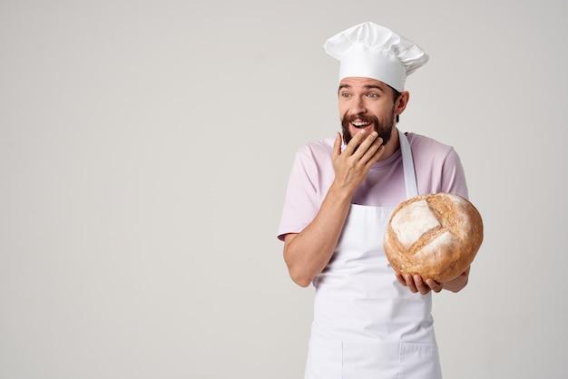 Piekarz w białym fartuchu z chlebem w rękach profesjonalistów