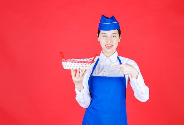 Piekarz w niebieskim fartuchu trzymający kosz na chleb z czerwonym ręcznikiem w środku.