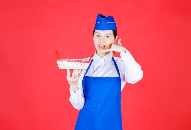 Piekarz w niebieskim fartuchu trzymający koszyk na chleb z czerwonym ręcznikiem w środku i proszący o telefon i zamówienie.