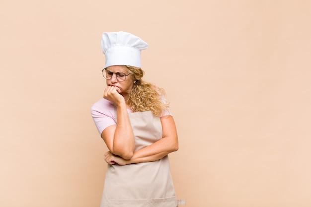 Piekarz w średnim wieku czująca się poważna, zamyślona i zaniepokojona, wpatrzona w bok z ręką przyciśniętą do brody