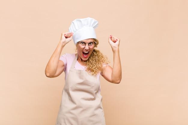 Piekarz w średnim wieku czująca się szczęśliwa, zaskoczona i dumna, krzycząca i świętująca sukces z wielkim uśmiechem