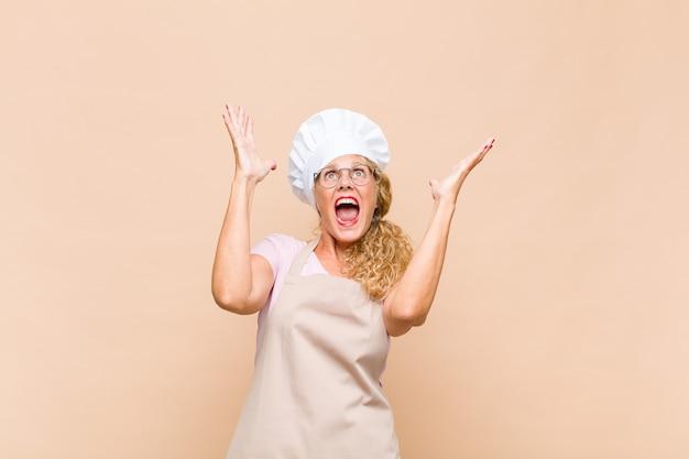 Piekarz w średnim wieku czująca się szczęśliwa, zdumiona, szczęśliwa i zdziwiona, świętująca zwycięstwo z obiema rękami uniesionymi do góry