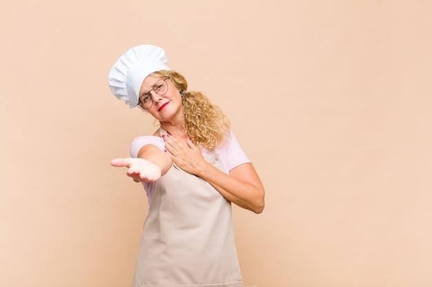 Piekarz w średnim wieku czuje się szczęśliwa i zakochana, uśmiecha się z jedną ręką przy sercu, a drugą wyciągniętą do przodu