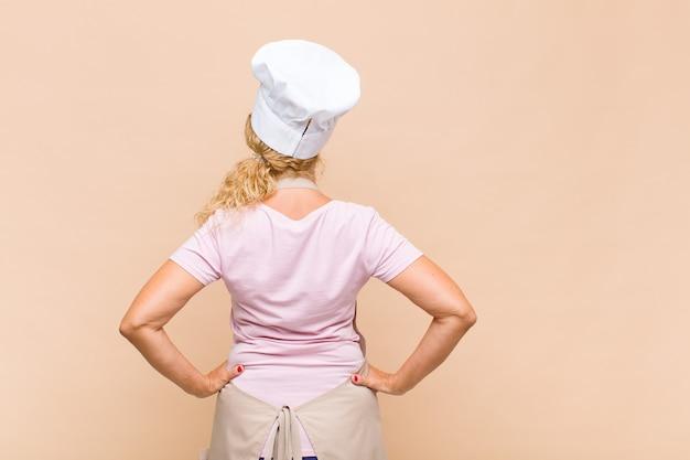 Piekarz w średnim wieku czuje się zagubiona lub pełna lub ma wątpliwości i pytania, zastanawia się, z rękami na biodrach, widok z tyłu