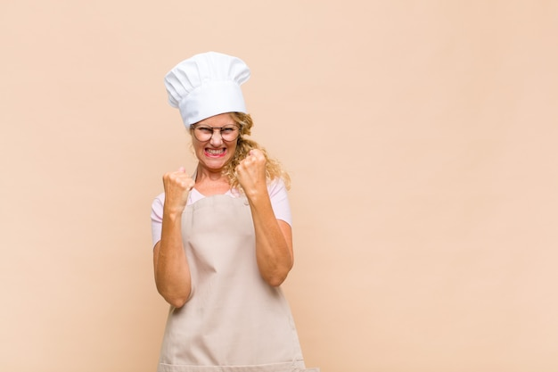 Piekarz w średnim wieku krzyczy triumfalnie, śmiejąc się i czując radość i podekscytowanie, świętując sukces