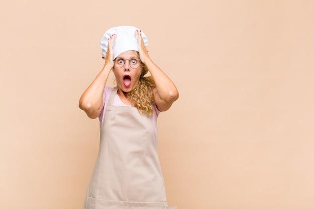 Piekarz w średnim wieku podnoszący ręce do głowy, z otwartymi ustami, czujący się wyjątkowo szczęśliwy, zaskoczony, podekscytowany i szczęśliwy
