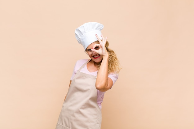 Piekarz w średnim wieku, uśmiechnięta radośnie ze śmieszną miną, żartująca i zaglądająca przez wizjer, podglądająca sekrety