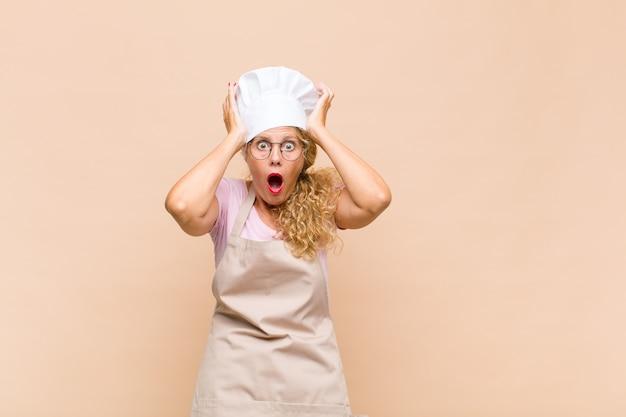 Piekarz w średnim wieku wygląda na podekscytowaną i zaskoczoną