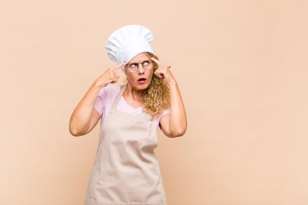 Piekarz w średnim wieku, wyglądająca na skoncentrowaną i intensywnie myślącą nad pomysłem, wyobrażającą sobie rozwiązanie wyzwania lub problemu