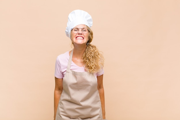 Piekarz w średnim wieku, wyglądająca na szczęśliwą i głupkowatą, z szerokim, zabawnym, szalonym uśmiechem i szeroko otwartymi oczami