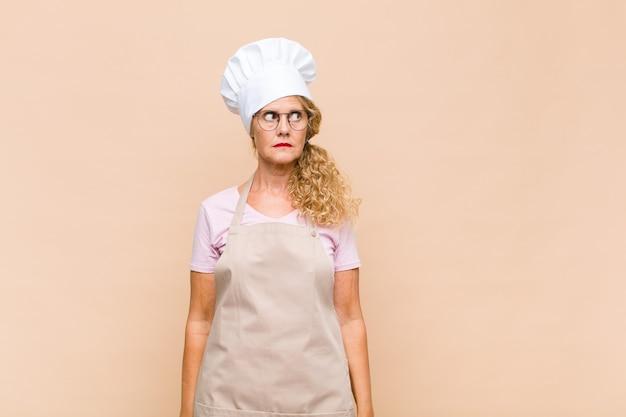 Piekarz w średnim wieku wyglądający na zmartwioną, zestresowaną, niespokojną i przestraszoną, panikującą i zaciskającą zęby