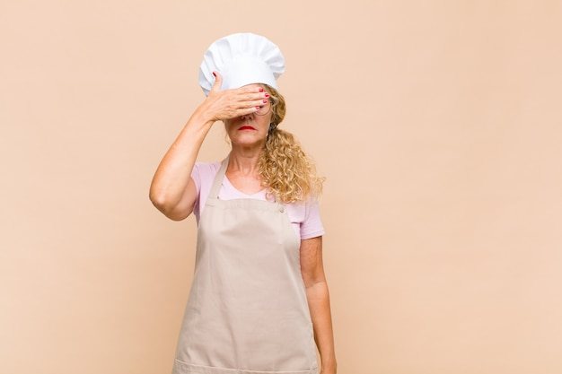 Piekarz w średnim wieku zakrywający oczy jedną ręką, przestraszony lub niespokojny, zastanawiający się lub na ślepo czekający na niespodziankę