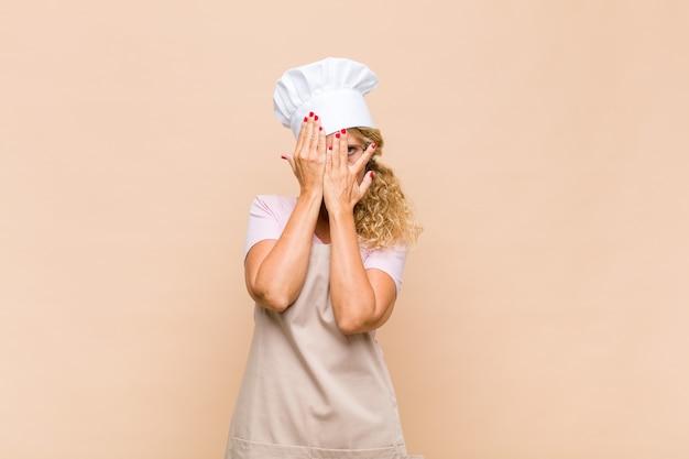 Piekarz w średnim wieku zakrywający twarz rękami, zaglądający między palce ze zdziwieniem i patrząc w bok