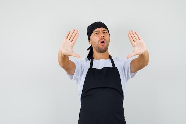 Piekarz w t-shircie, fartuch pokazuje gest odmowy i wygląda na zirytowanego