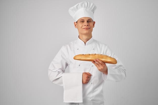 Piekarz w ubraniach szefów kuchni trzymający bochenek jedzenia świeżego