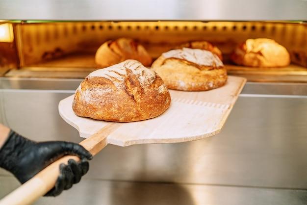 Piekarz wkłada chleb do pieca piekarniczego kuląc się na podłodze piekarni
