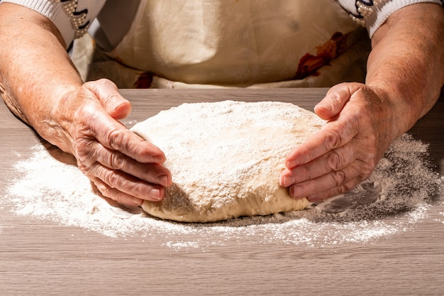 Piekarz wręcza robić ciastu na drewnianej desce w kuchni. kobieta prababka ugniata ciasto do domowego wypieku