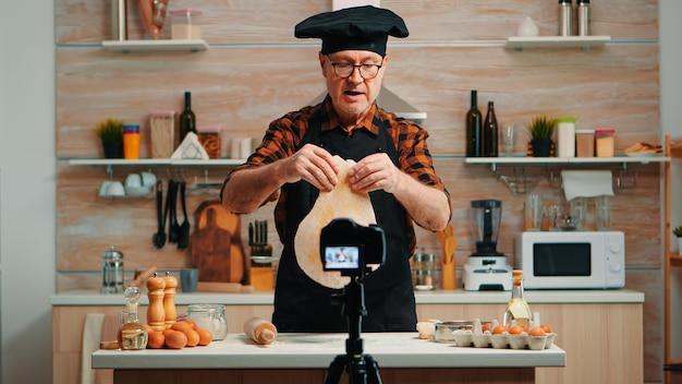 Piekarz za pomocą drewnianego wałka do ciasta przed kamerą wideo rejestrującą nowy odcinek gotowania. stary bloger, szef kuchni influencer, korzystający z technologii internetowej, komunikujący się w mediach społecznościowych za pomocą sprzętu cyfrowego