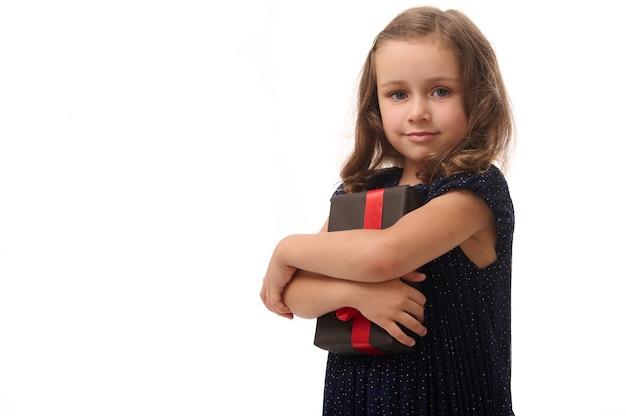 Piękna 4-letnia urocza dziewczynka delikatnie przytula czarne pudełko i uroczo patrzy w kamerę, stojąc na białym tle na białym tle z miejsca na kopię. koncepcja rocznicy i czarnego piątku