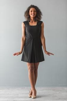 Piękna afro amerykańska dziewczyna w czarnej koktajl sukni.