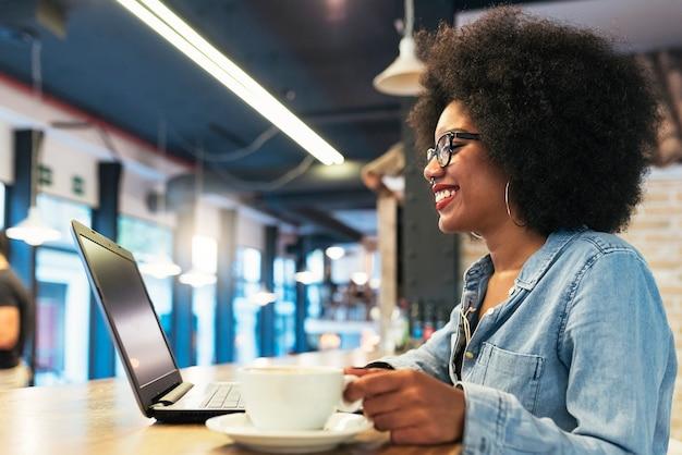 Piękna afro amerykańska kobieta za pomocą telefonu komórkowego i laptopa w kawiarni. koncepcja komunikacji.