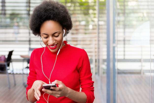 Piękna afro czarna kobieta jest ubranym słuchawki słucha muzyka online przez smartphone