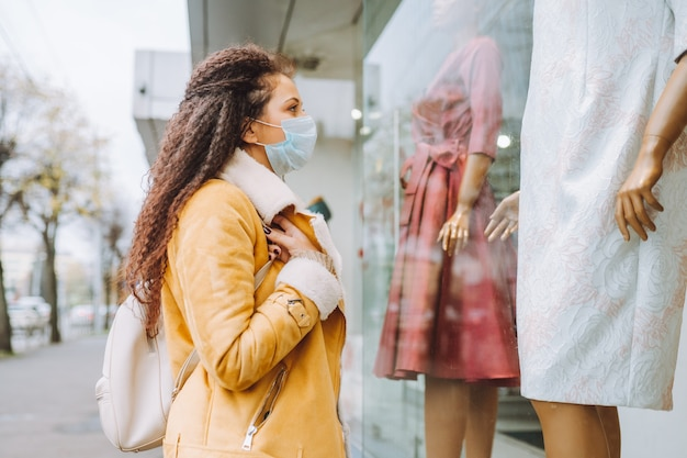 Piękna afro włosa kobieta ubrana w ochronną medyczną maskę na twarz stoi na ulicy miasta i patrzy na wystawę sklepową.