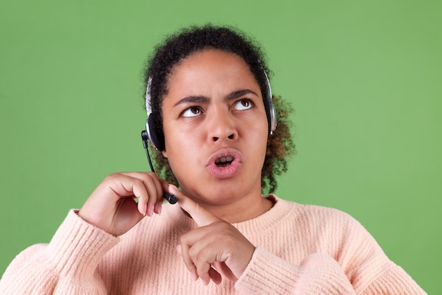 Piękna afroamerykanka na zielonej ścianie kierownik call center pracownik sprawdzający mikrofon