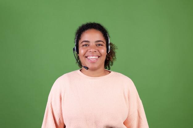 Piękna afroamerykanka na zielonej ścianie kierownik call center pracownik szczęśliwy uroczy uśmiechnięty witający wszystkie połączenia