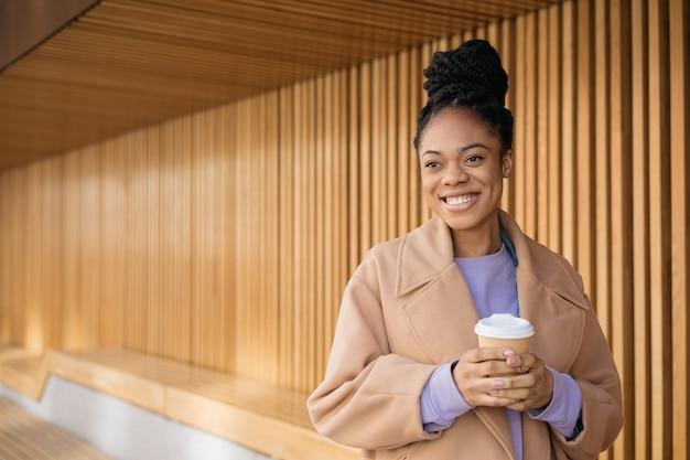 Piękna afroamerykanka pijąca kawę odwracająca wzrok spacerująca po ulicy kopia przestrzeń