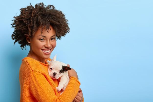 Piękna afroamerykanka stoi bokiem, bawi się w domu małym buldogiem, okazuje miłość między właścicielem a zwierzakiem