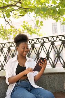 Piękna afroamerykanka w zwykłych ubraniach używa smartfona i uśmiecha się stojąc przy oknie