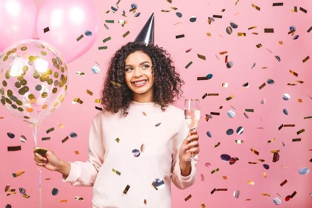 Piękna afroamerykanka z różową koszulką z kolorowymi balonami