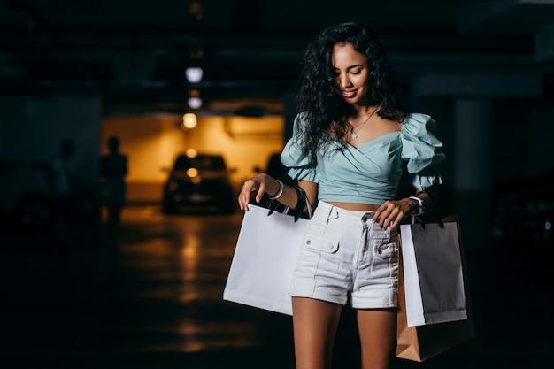 Piękna afroamerykańska dziewczyna stojąca na deskorolce z torby na zakupy w podziemnym parkingu