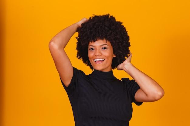 Piękna afroamerykańska dziewczyna z uśmiechem afro fryzura. kobieta z czarnymi, mocnymi włosami do reklamy szamponu