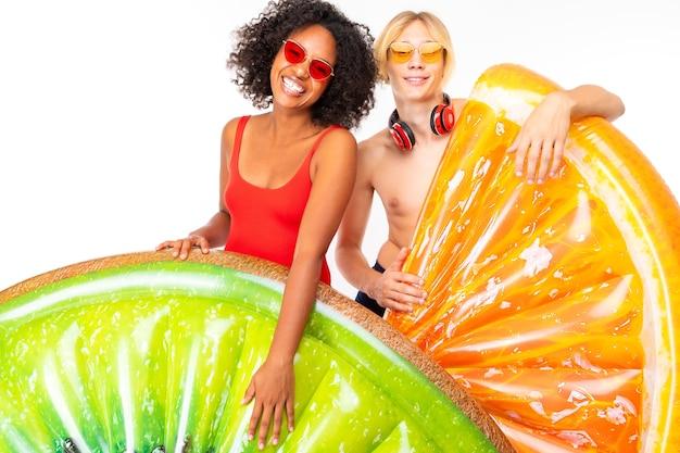 Piękna afroamerykańska kobieta i przystojny kaukaski mężczyzna z krótkimi jasnymi włosami w kostiumie kąpielowym stoją z dużymi gumowymi materacami plażowymi
