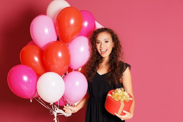 Piękna afroamerykańska kobieta w imprezowej czapce z balonami i prezentem na kolorowym tle