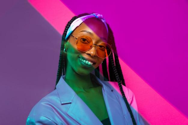 Piękna afroamerykańska kobieta z fryzurą afro warkoczykami i stylowymi ubraniami - portret młodej czarnej dziewczyny w studio