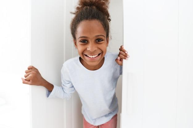 Piękna afroamerykańska mała dziewczynka uśmiecha się i bawi się w chowanego w szafie w domu