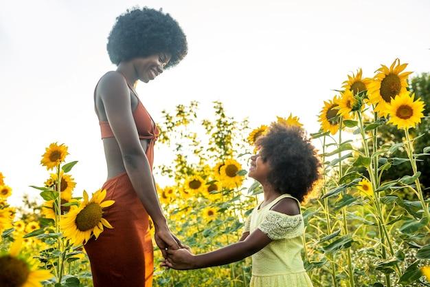 Piękna afroamerykańska mama i córka bawią się i bawią na polu słoneczników