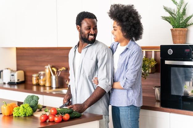 Piękna afroamerykańska para gotuje w domu - piękna i wesoła czarna para przygotowuje wspólnie obiad w kuchni