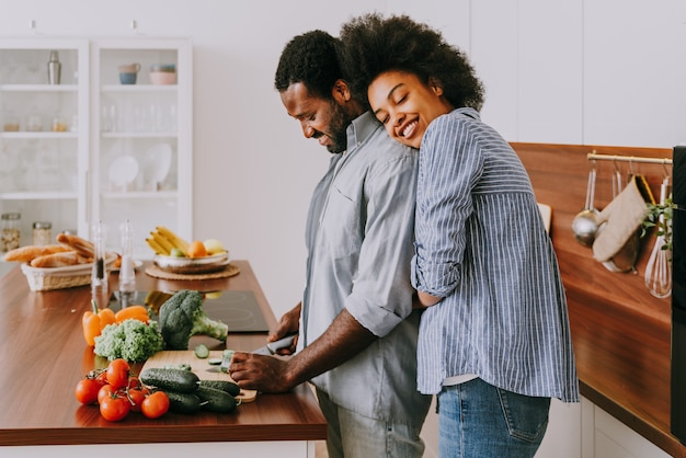 Piękna Afroamerykańska Para Gotuje W Domu - Piękna I Wesoła Czarna Para Przygotowuje Wspólnie Obiad W Kuchni Premium Zdjęcia