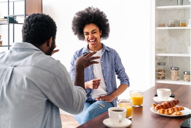 Piękna afroamerykańska para je razem śniadanie w domu - wesoła czarna para spędza razem czas rano
