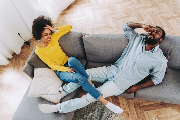 Piękna afroamerykańska para relaksuje się na kanapie w domu - życie domowe, wesoła para łączenie się i zabawa w salonie
