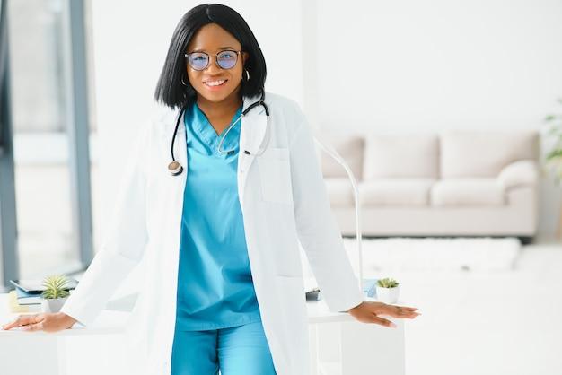 Piękna afrykańska amerykańska pielęgniarka pediatryczna w nowoczesnym biurze