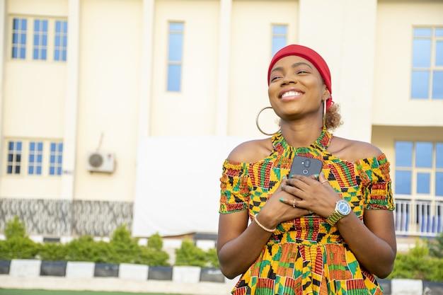 Piękna afrykańska dama trzymająca telefon przy piersi wypełniona radością