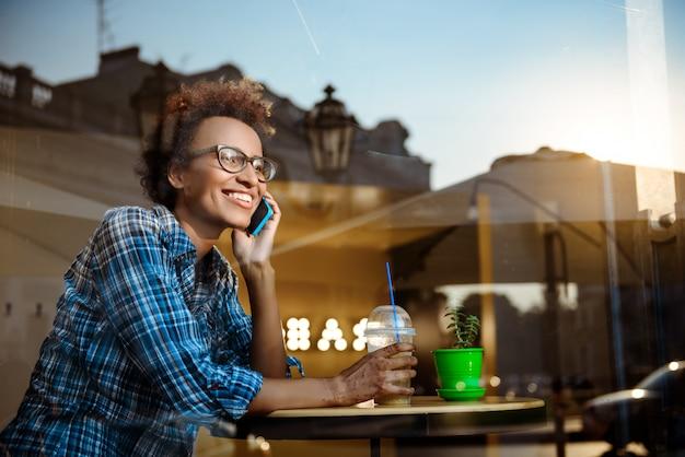 Piękna afrykańska dziewczyna uśmiecha się, mówiąc na telefon, siedząc w kawiarni. strzał z zewnątrz.