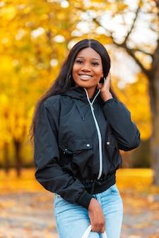 Piękna afrykańska dziewczyna w kurtce i dżinsach spacerująca po parku ze złotymi jesiennymi liśćmi